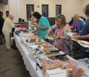 Faculty and staff fill their plates at the buffet table