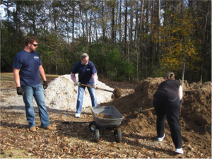 Volunteers shovel soil into a cart