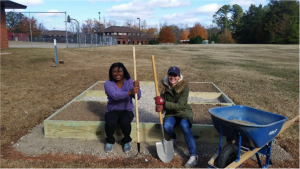Two volunteers hold a rake and shovel