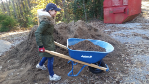 A volunteer pushes a wheel barrow filled with soil