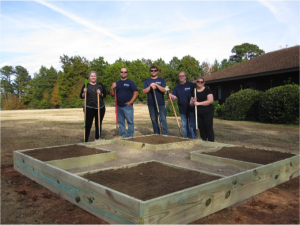 Volunteers next to raised planting beds filled with soil